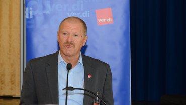 Portrait Bezirksgeschäftsführer Berthold Leinweber spricht am Mikro vor ver.di Stellwand