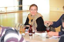 Natalie Jopen sitzt am Tisch, lächelt schelmisch in die Kamera