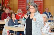 Delegierte steht mitten im Saal mit Mikrofon in der Hand.