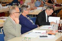 3 Delegierte von rechts. Sie schreiben in ihre Unterlagen oder hören dem Vortrag zu.