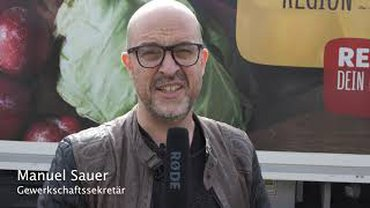 POrtrait GS Manuel Sauer mit Mikro vor Rewe Breuna